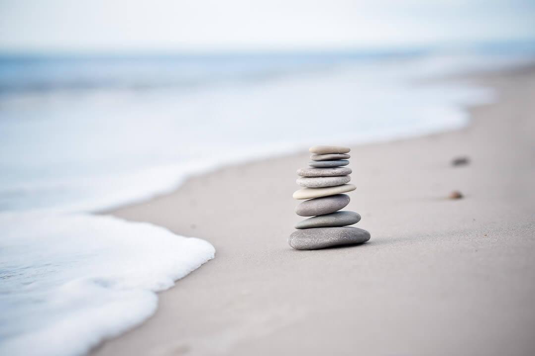 Stenar balanserar på sandstrand vid hav